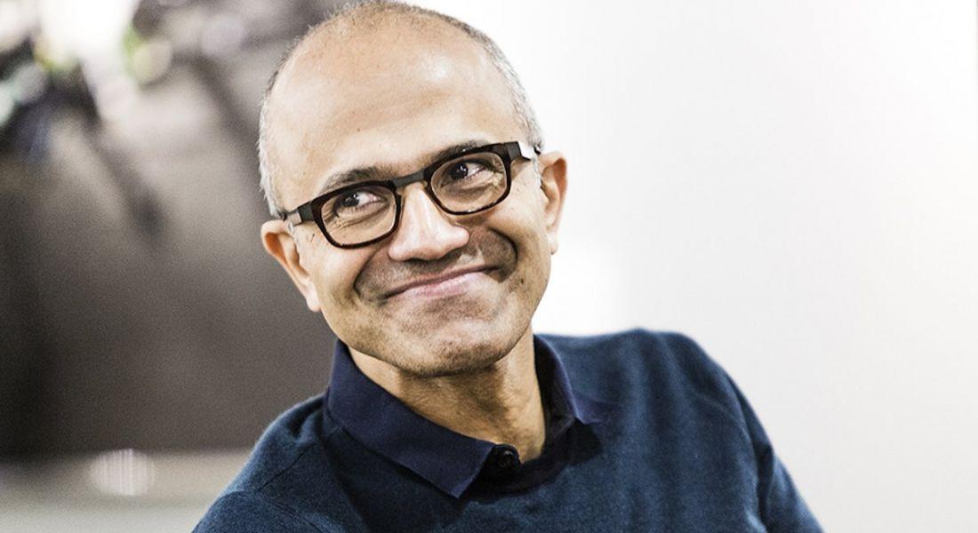 CEO of Microsoft, Satya Nadella, smiling while looking off camera.