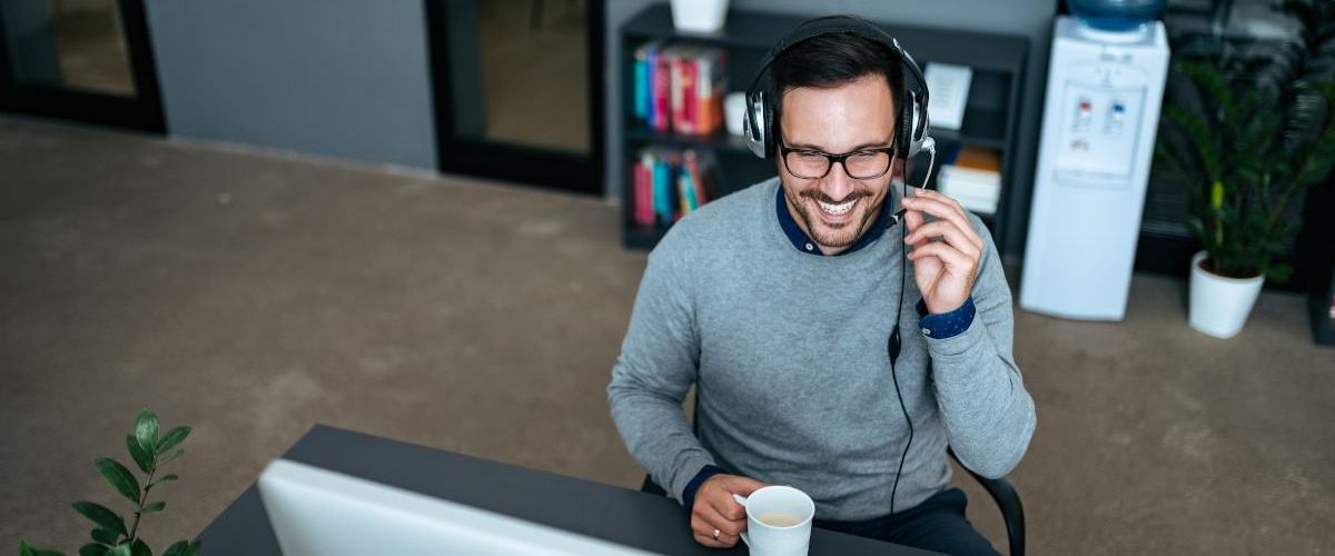 A man wearing a headset while holding a cup of coffee in front of a large computer screen. He is smiling at the screen.