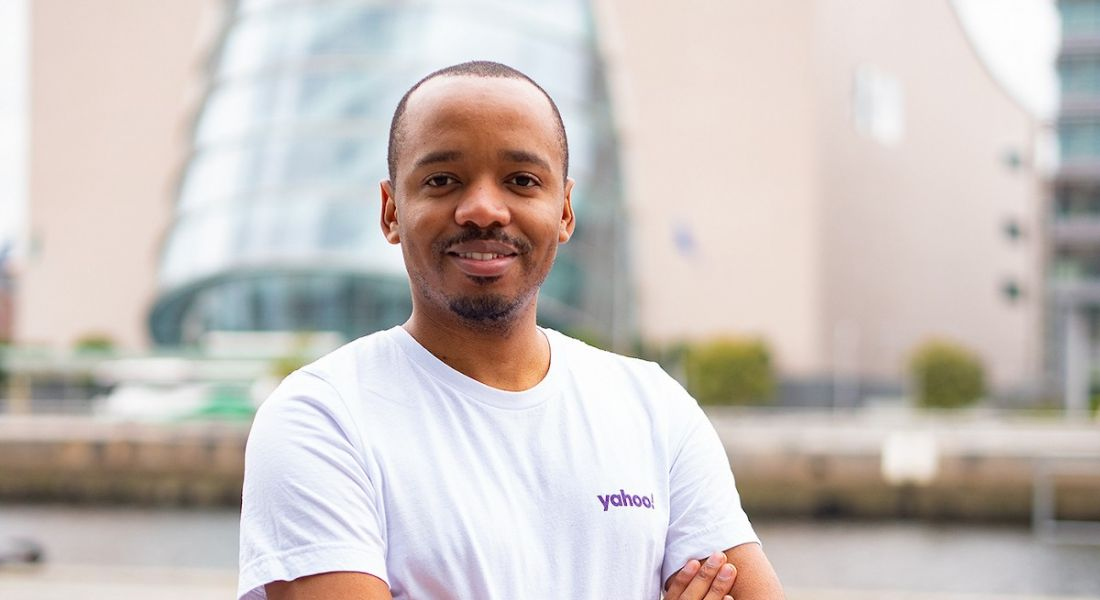 A young man in a white T-shirt with the Yahoo logo on the left breast. He's smiling at the camera with a cityscape in the background.