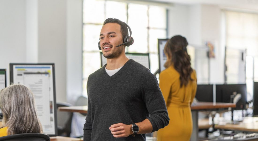 A person is walking through a bright office space, wearing a headset.