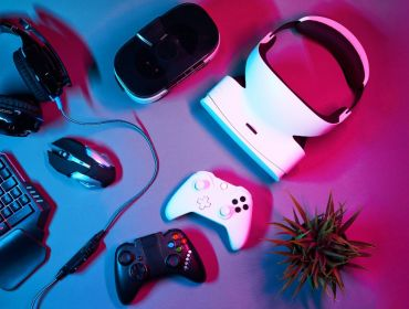 Several gaming devices including controllers, headphones and a VR headset, sitting on a blue and pink neon-lit table.