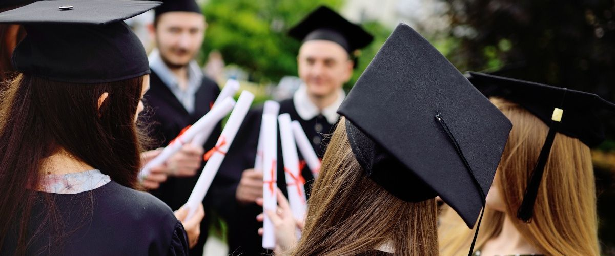 A group of graduates gathered in a circle wearing caps and gowns and holding rolled certificates.