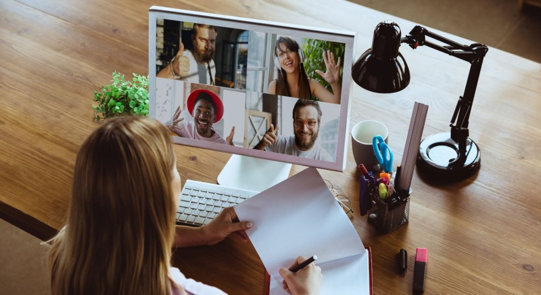 A woman working at a desk with a large monitor displaying four people on a virtual call, showing hybrid working.