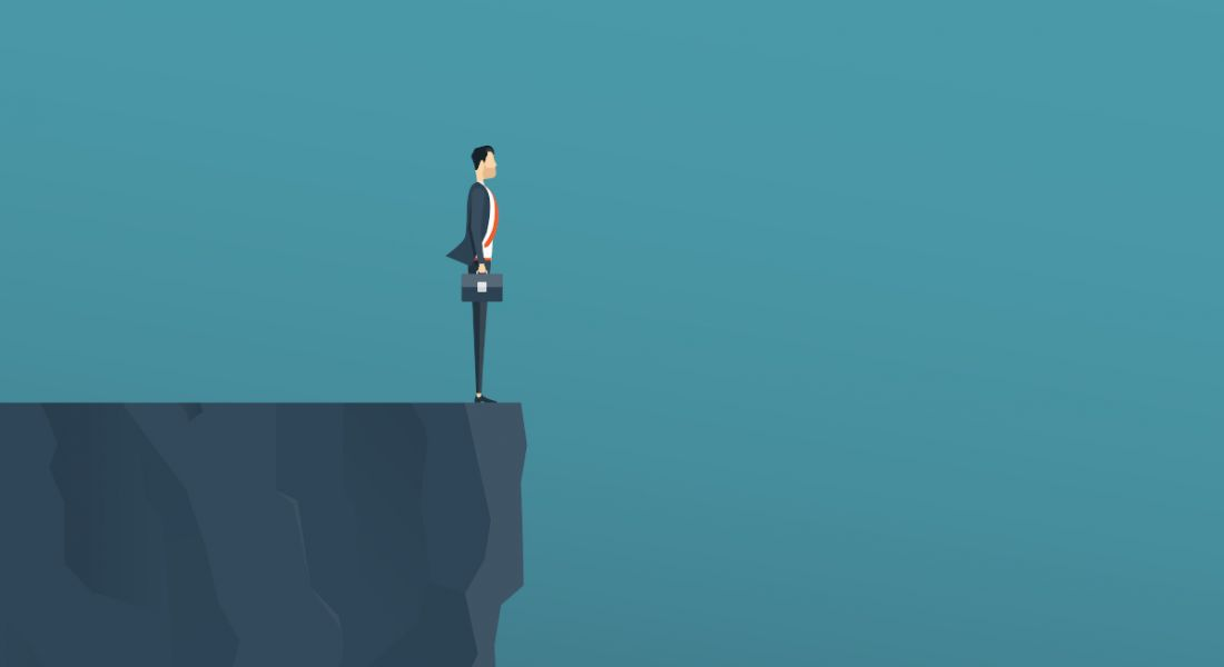A graphic of a man in a suit holding a briefcase standing at the edge of a cliff against a dark blue background, symbolising a hiring cliff.