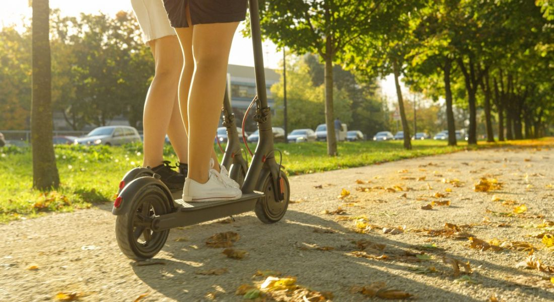 Two people can be seen riding on e-scooters. They are on a path and surrounded by trees. There is a warm glow from the sun which is casting a shadow in the direction of the photographer. Only the lower halves of the people are visible.