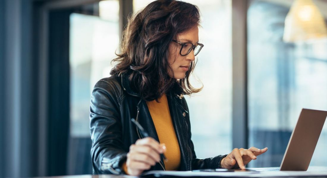 A woman with dark hair and glasses sits at desk working on a laptop, while taking notes beside it.