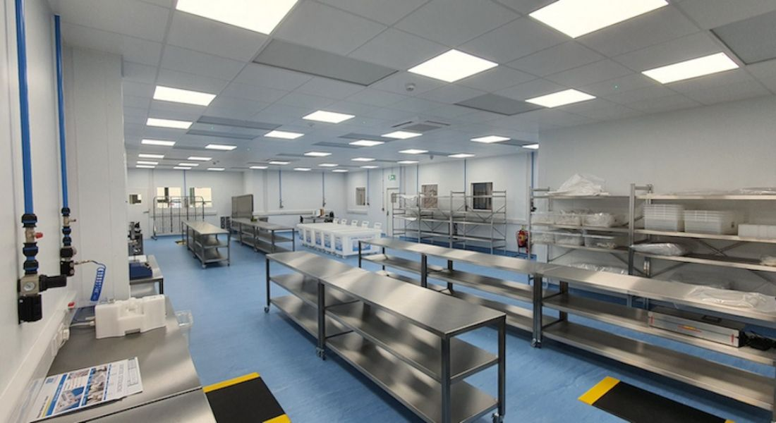 The Watson-Marlow facility is shown. There are long, steel tables throughout the room and laboratory equipment on shelves against the walls.