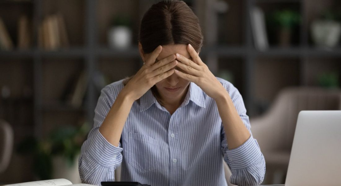 Young woman distressed with hand on head while working at a desk.