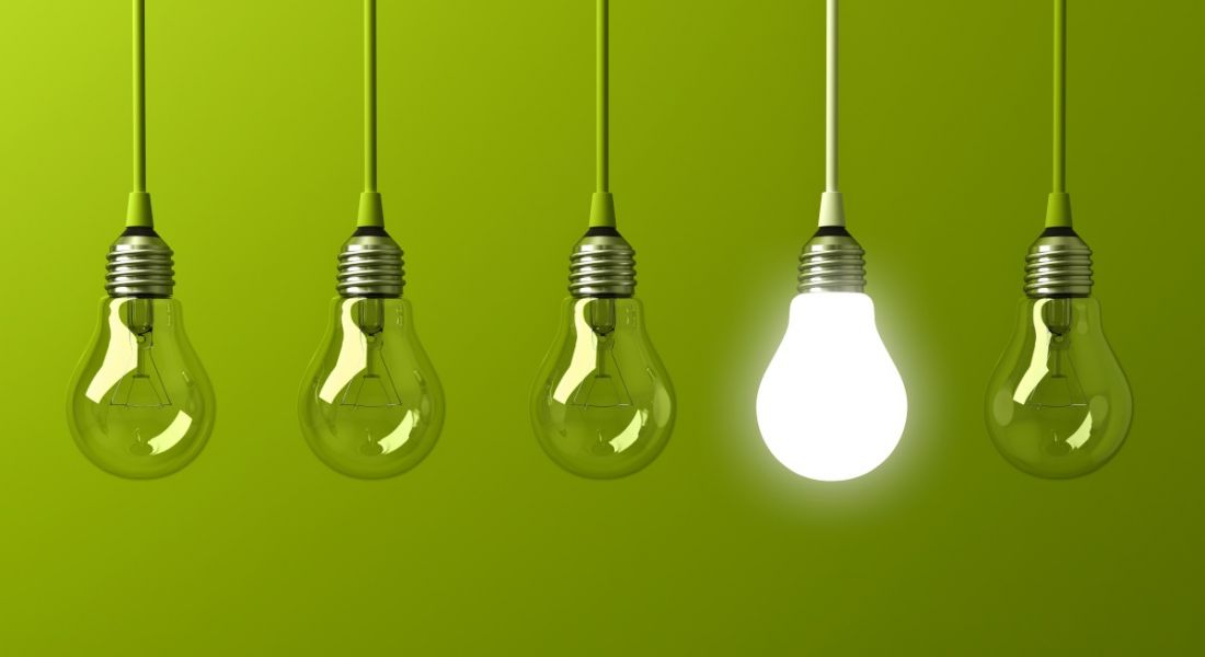 Five lightbulbs are hanging against a green background. One is lit up, making it stand out from the crowd.