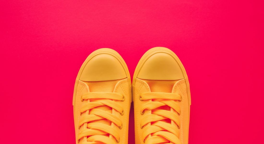 Bright yellow tennis shoes against a bright red background, symbolising taking your first step towards working in data.
