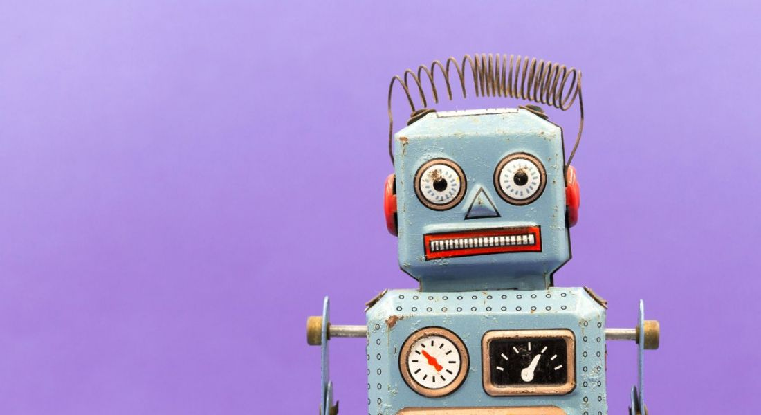 A vintage toy robot is standing against a purple background, symbolising automation and digital co-workers.