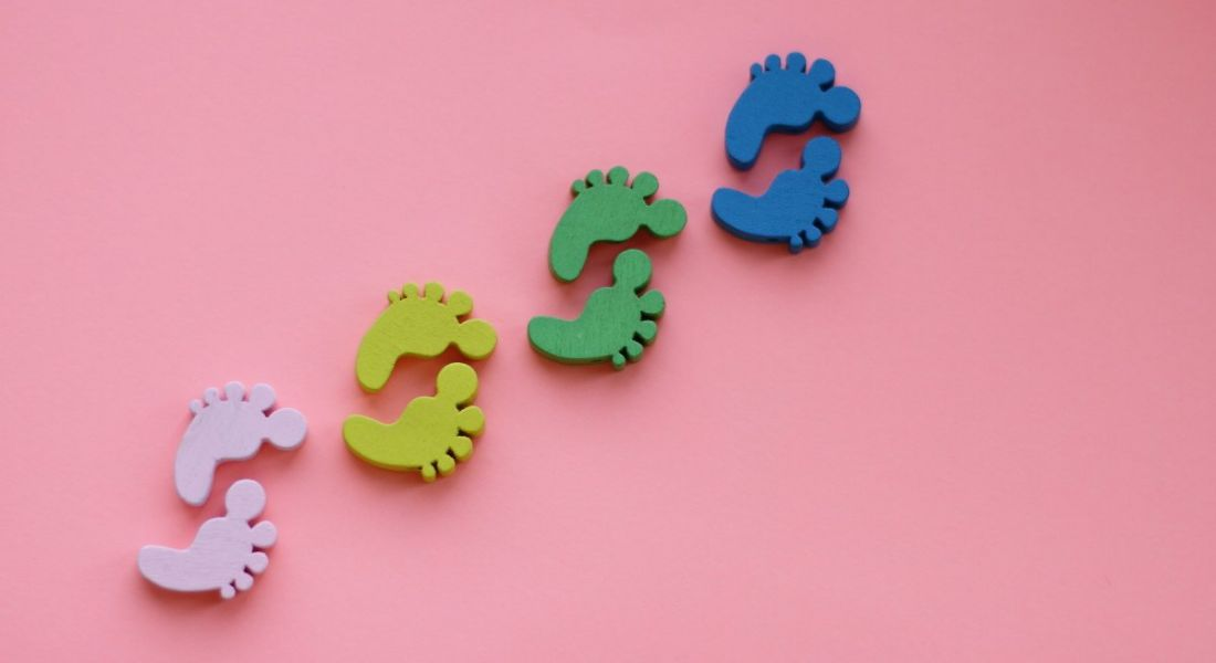 Pink, yellow, green and blue footprints against a pink background, symbolising first steps.
