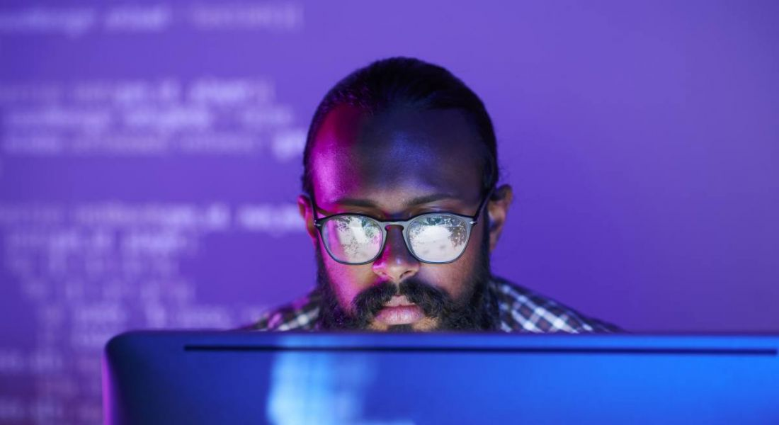 A man is doing work in data, looking at code on his computer in a dark room with a purple glow.