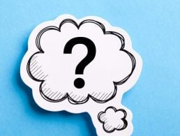 Small wooden figures have speech bubbles over their heads on a grey background.