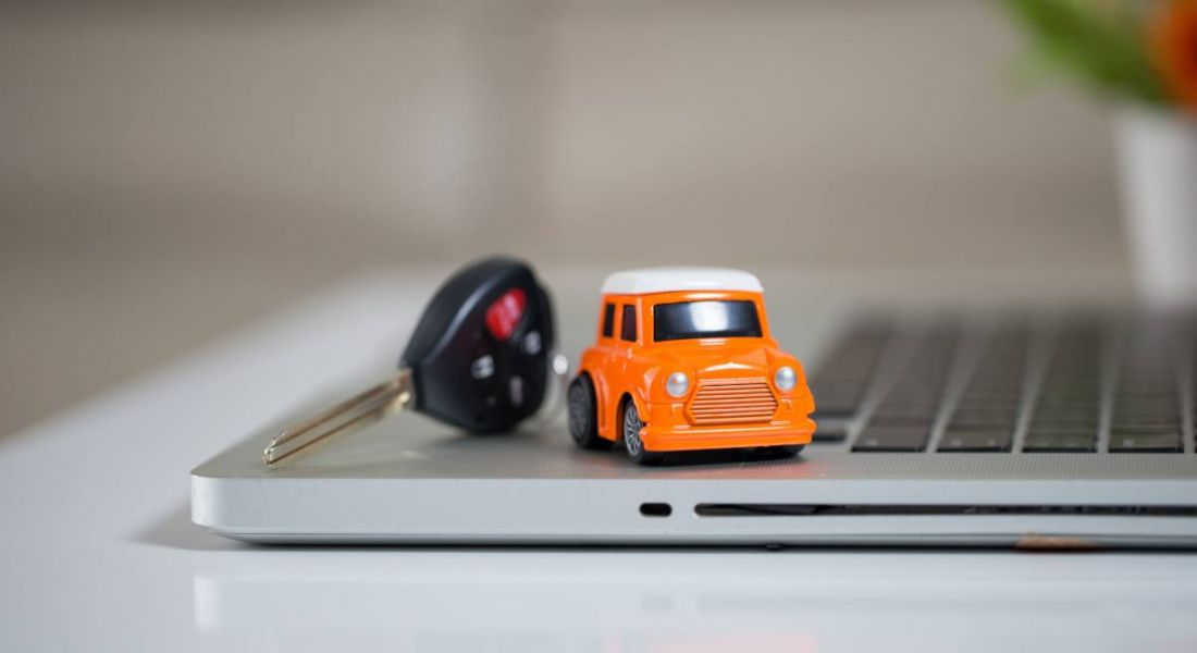 An orange toy mini cooper car is sitting next to a car key on a laptop.