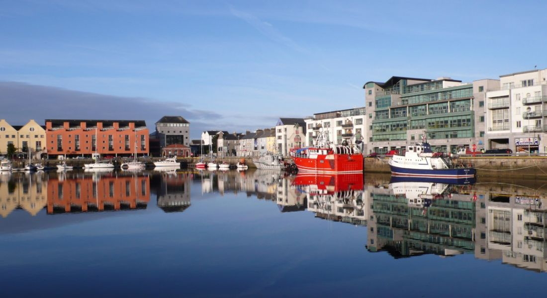 A still quay in Galway on a clear day, with boats docked, surrounded by buildings.