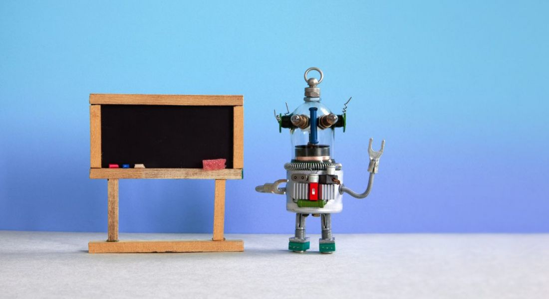 A toy robot is standing next to a blackboard against a blue background.