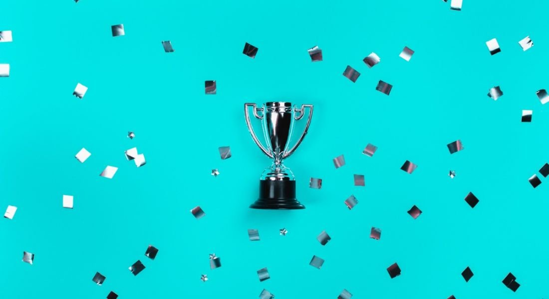A silver trophy is laying against a blue background where it is surrounded by silver confetti.