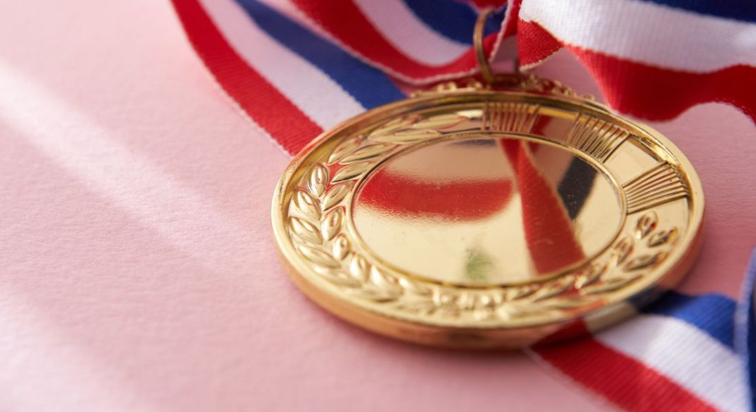Close-up of a gold medal resting on a pink background.