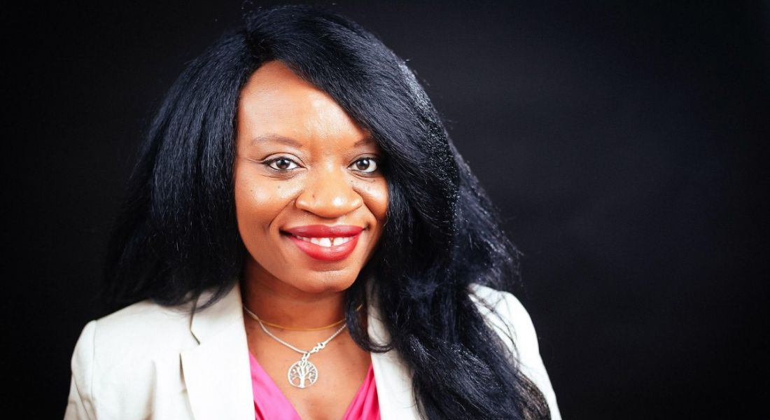 A close-up headshot of Anie Akpe wearing a pink top and white blazer against a black background.