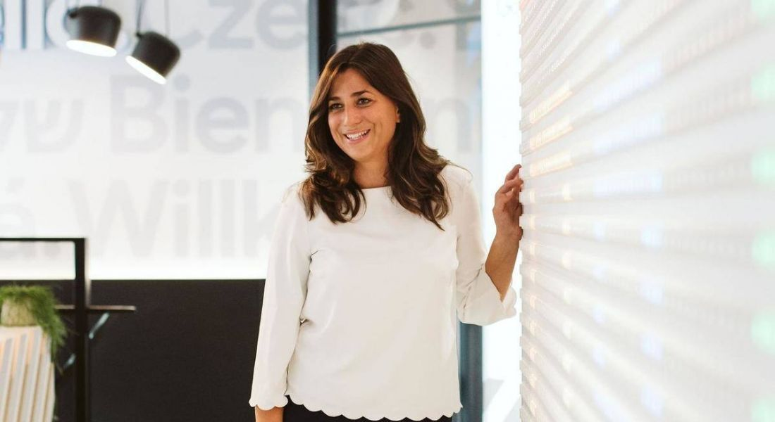 Anna Brailsford, CEO of Code First Girls, stands beside a wall wearing a white top, smiling off camera.