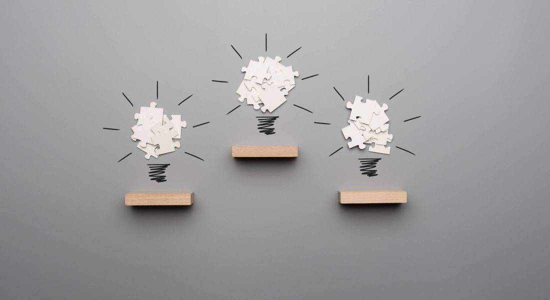 Three wooden shelves sit against a grey background. Above each, is a group of white jigsaw puzzle pieces with a black squiggle underneath in the shape of a lightbulb.