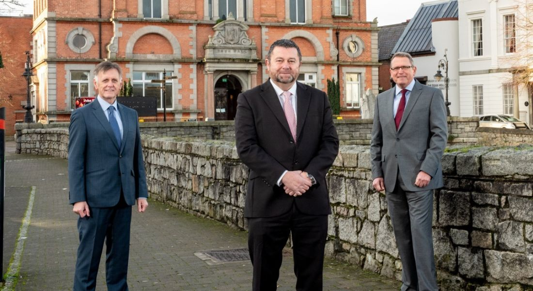 Three men in suits are standing outdoors in front of a large red brick building.