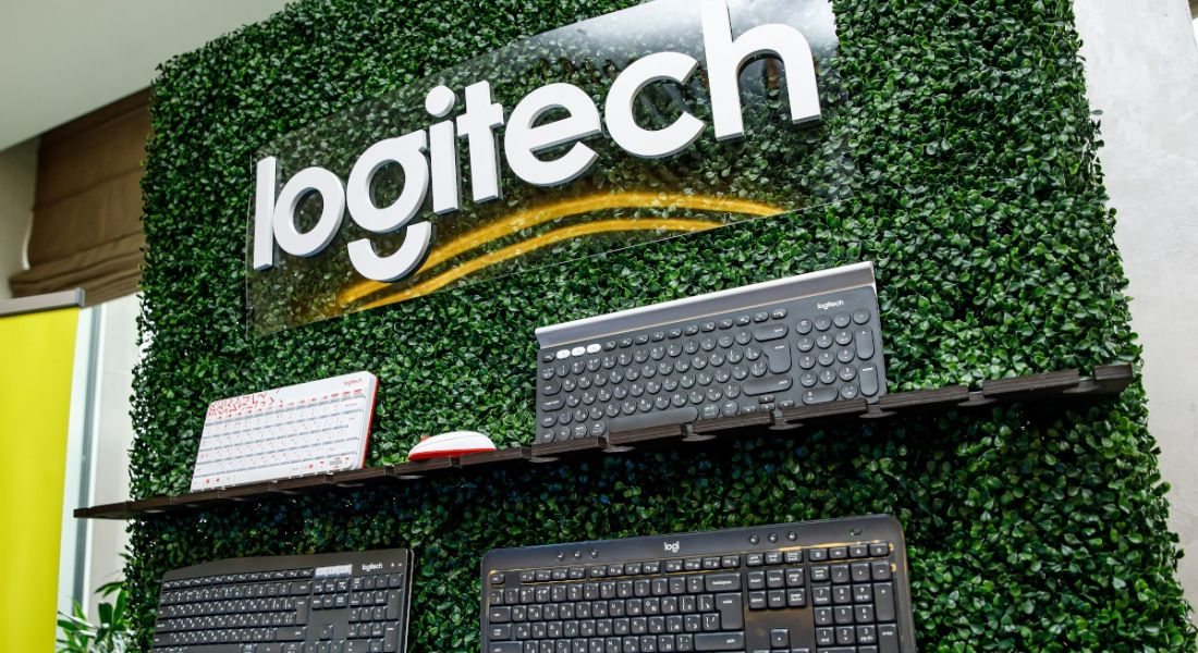 A wall display of four computer keyboards against a backdrop of greenery. The Logitech logo is displayed above the keyboards.