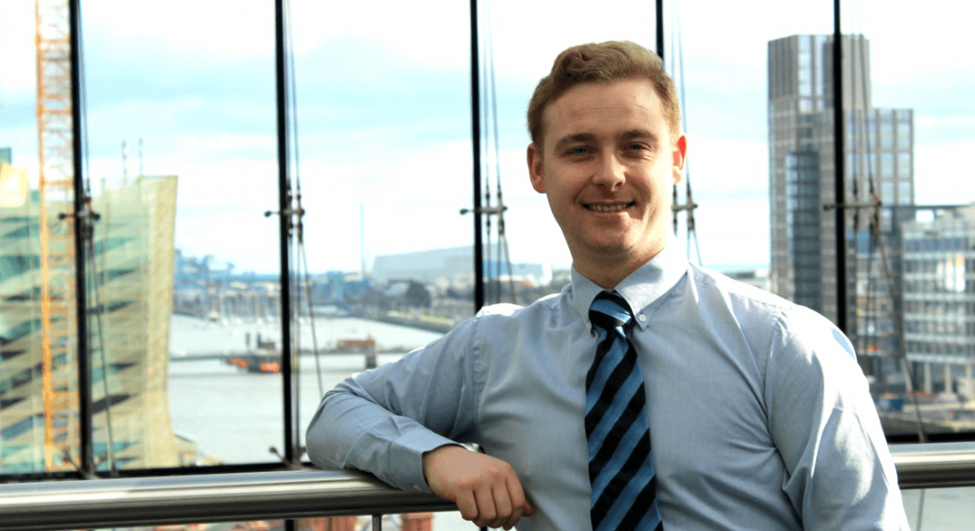 Stuart Larner is standing at a window overlooking the river Liffey in Dublin on a bright day, wearing a shirt and tie and smiling into the camera.