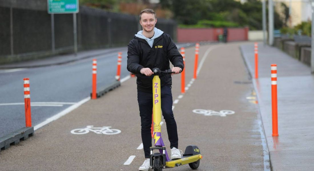 Charlie Gleeson stands by an e-scooter on a bike lane in Dublin.