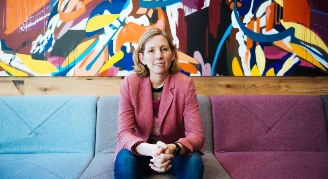 Medb Corcoran of Accenture Labs is sitting on a colourful couch in a colourful room, smiling into the camera.