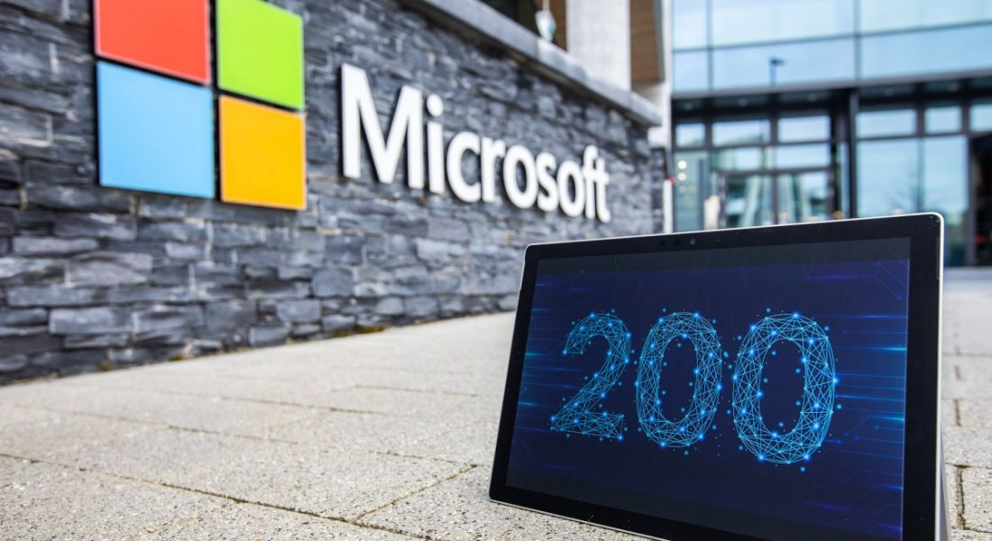A tablet displaying the number 200 is photographed in front of a wall bearing the Microsoft logo, leading into the company's Dublin campus.