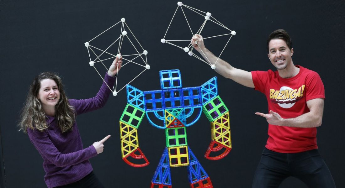 A woman and a man stand either side of a colourful 3D robot made out of cubes, while holding white cube structures in the air over the robot's head.