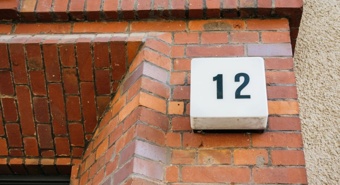 A number 12 sign on a brick wall of a house, beside the front door.