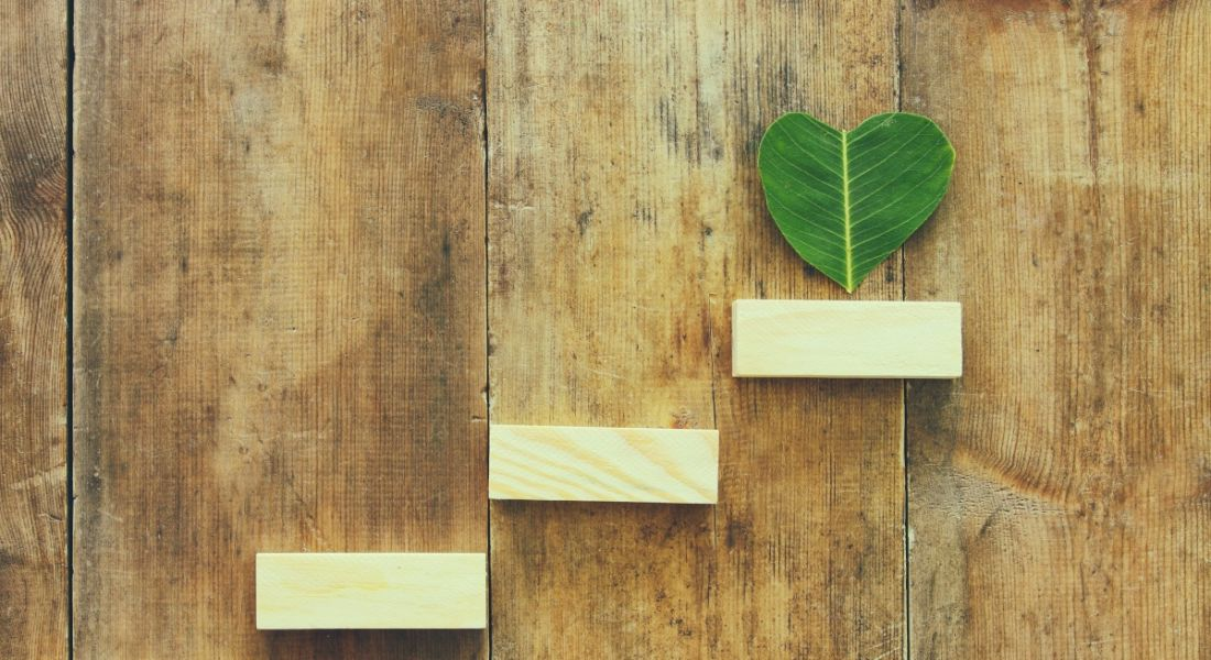 Wooden steps are leading up to a heart-shaped leaf against a wooden background.
