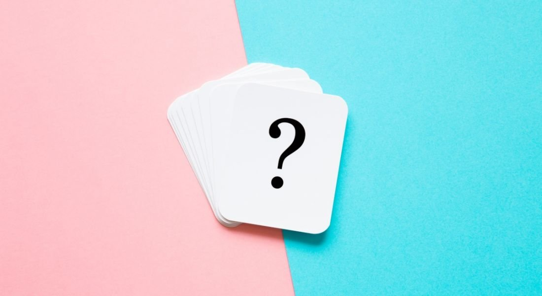 A stack of white playing cards are lying against a pink and blue background. The top card is showing a question mark.