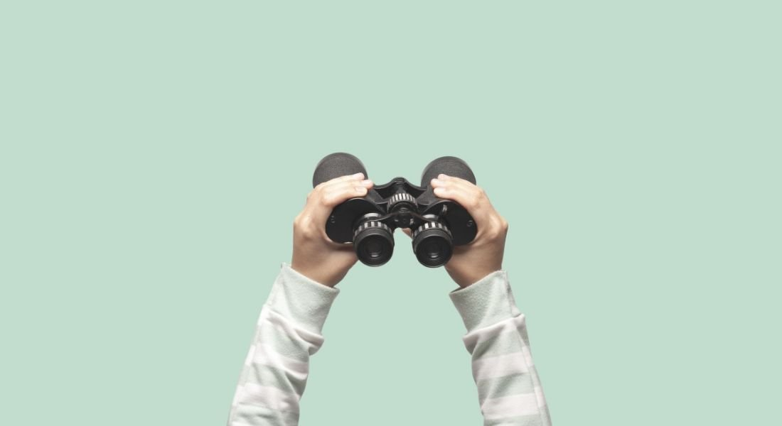 Hands are holding up binoculars against a plain green background.