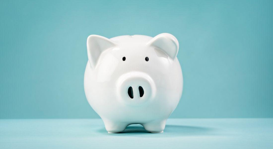 A white piggy bank sitting against a plain blue background.