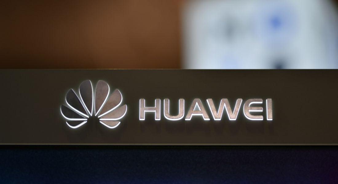 A backlit Huawei logo on a dark surface.