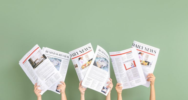 Three pairs of arms are holding up newspapers against a green background, symbolising jobs announcements.