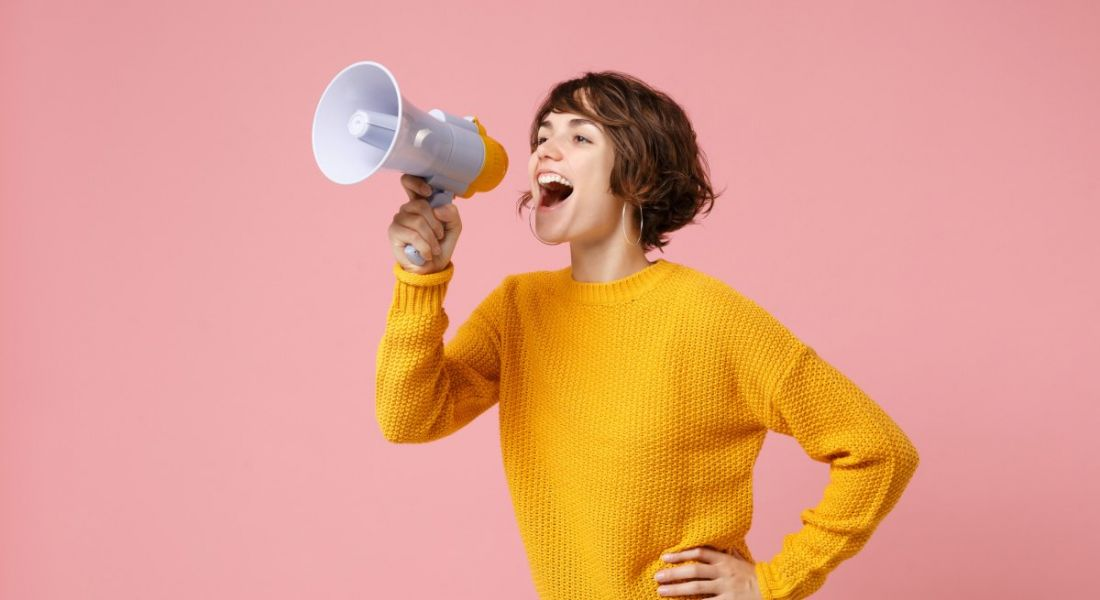 A woman with short hair and a yellow jumper is shouting into a megaphone.