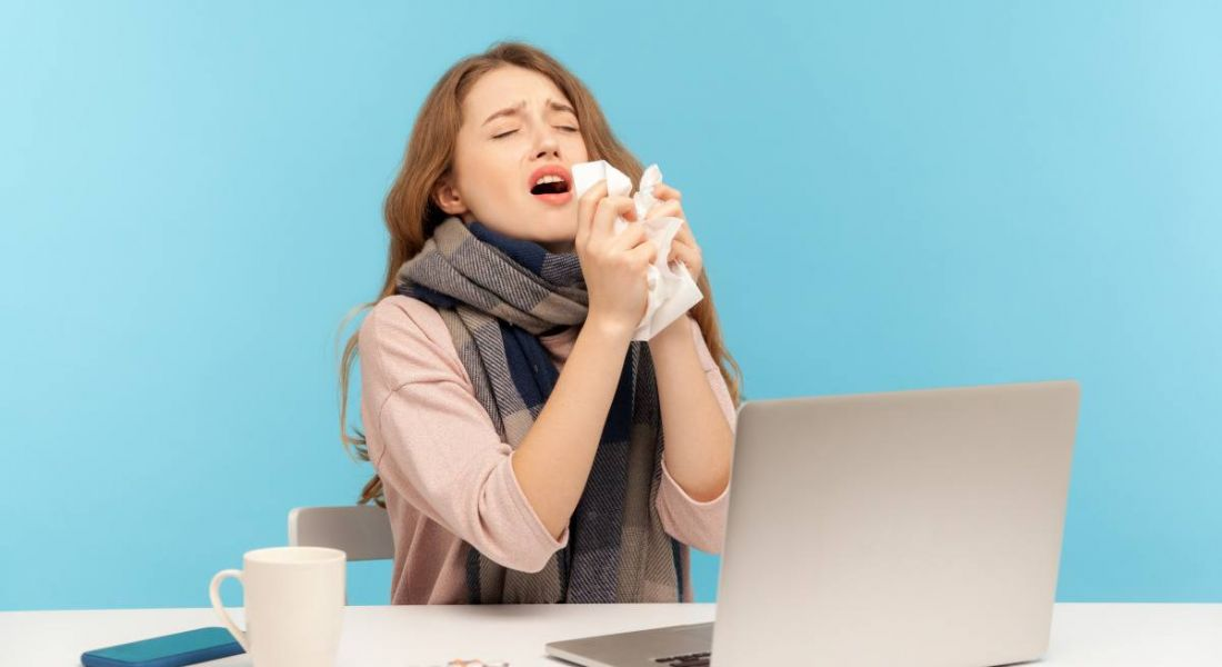 A woman is sneezing while working on her laptop.