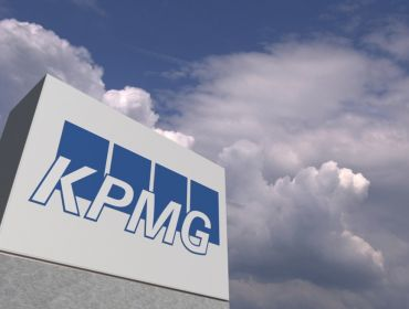 A KPMG company sign is photographed against a blue sky with clouds.