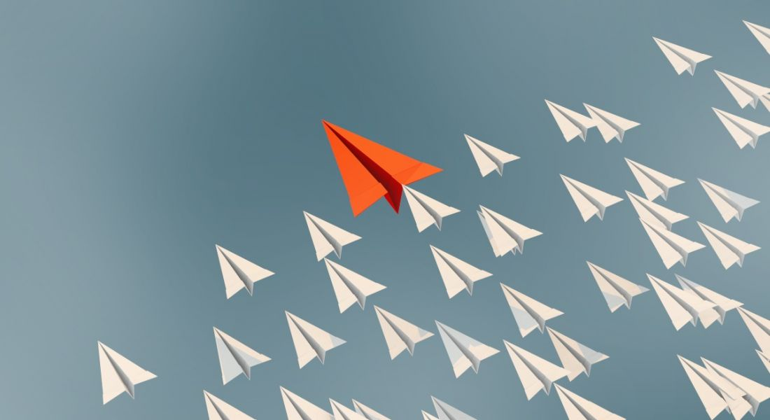 An illustration of a red paper plane flying ahead of a bunch of white paper planes, symbolising leadership.