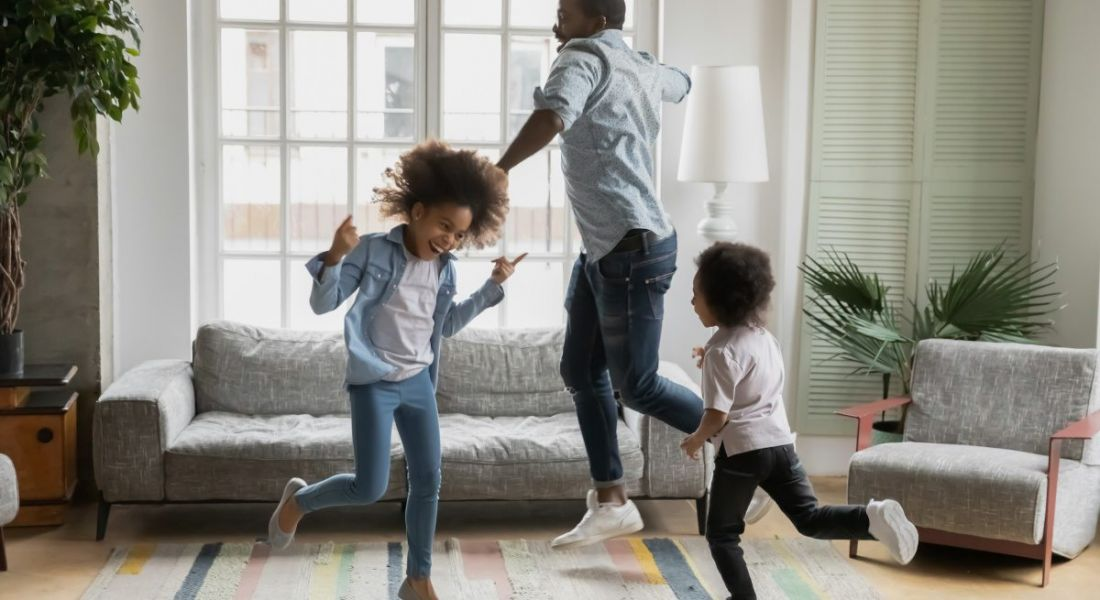A father is getting his two children to move more at home, dancing and laughing in a bright living room.