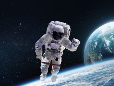 An astronaut is floating in space with the Earth and moon visible behind them.