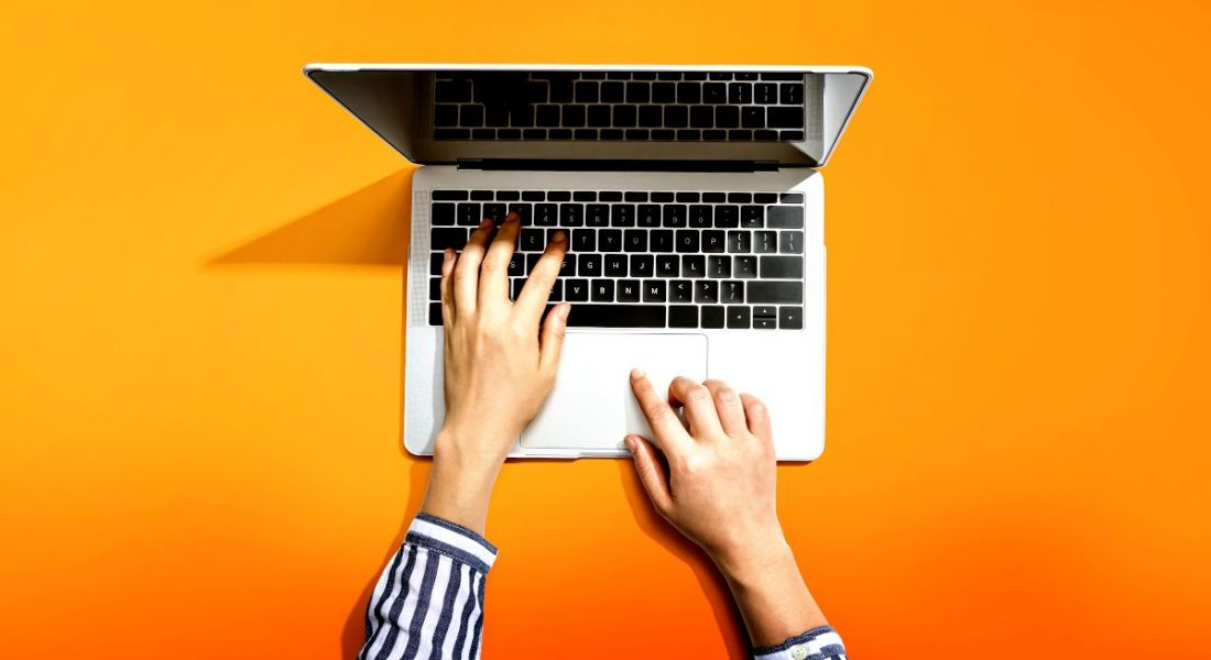 Overhead shot of a person in a striped shirt using a laptop against a vibrant orange background.