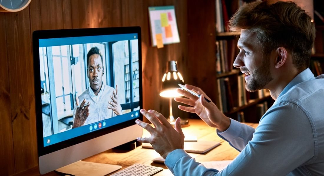 Two men are talking on a video call while working remotely.