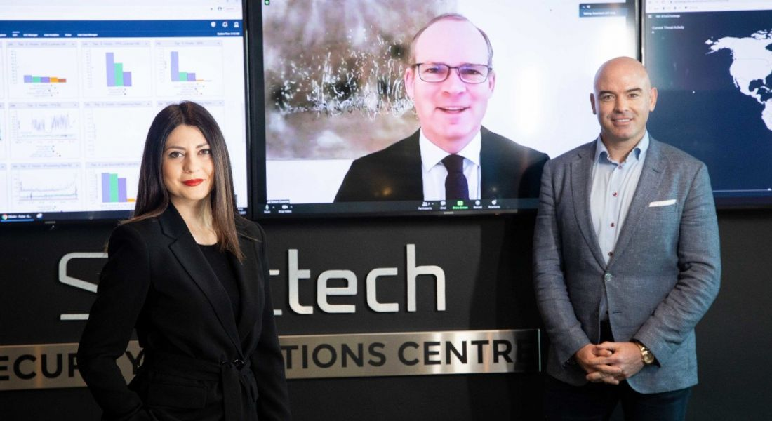 Raluca Saceanu and Ronan Murphy stand in front of a Smarttech247 logo with a large screen in between them. Minister Simon Coveney is on the screen.