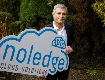 Ray Ryan, managing director of The Noeldge Group stands outside wearing a suit and holding a sign with the company's logo.